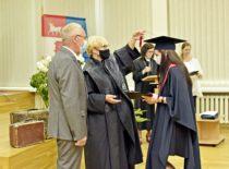 Absolventė gauna diplomą